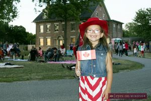 Young girl holds up Canadian flag in front of historic Fort Malden in Amherstburg just before the annual Canada Day fireworks.