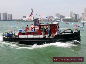 tug boat racing down detroit river crew waving