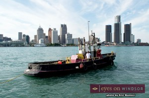 Boat on Detroit River pulls rope out for Tug Across The River 2014.