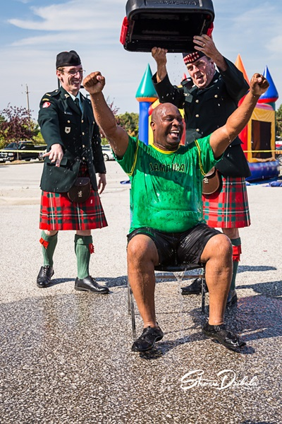 Drum Magor Xavier Allen raises arms after taking Ice Bucket Challenge with Pipe Major Peter Olsen, and Drummer Jim Carr of the Essex and Kent Scottish Pipes and Drums Band at 4th Annual Trot With The Troops