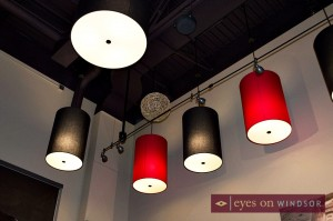 Red and black cylindrical lamps hang from the ceiling.
