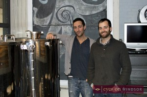 Brew Windsor Brewers and Spokespersons Joshua Goure and Jordan Goure  in front of brewing equipment.