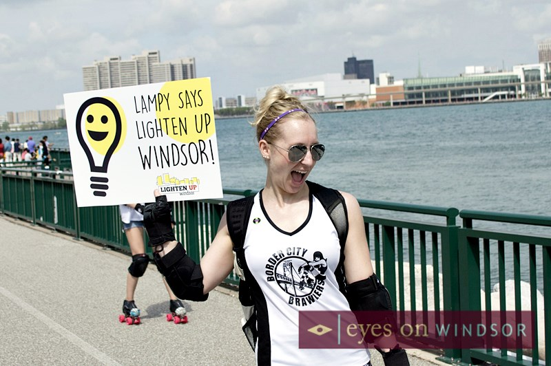Border City Brawlers' Karlene Nielsen hold's up Lighten Windsor sign during annual Mayor's Walk.