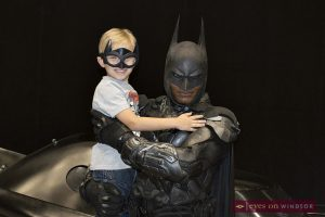 The Dark Knight holds young boy as they take a photo together at Windsor ComiCon.