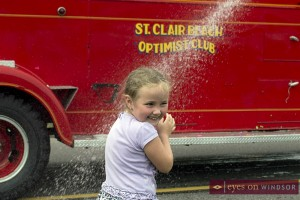 fire truck hose wets young girl at Tecumseh Corn Festival Parade