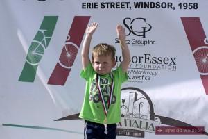 young boy celebrates finishing at the 57th Annual Tour di via Italia.