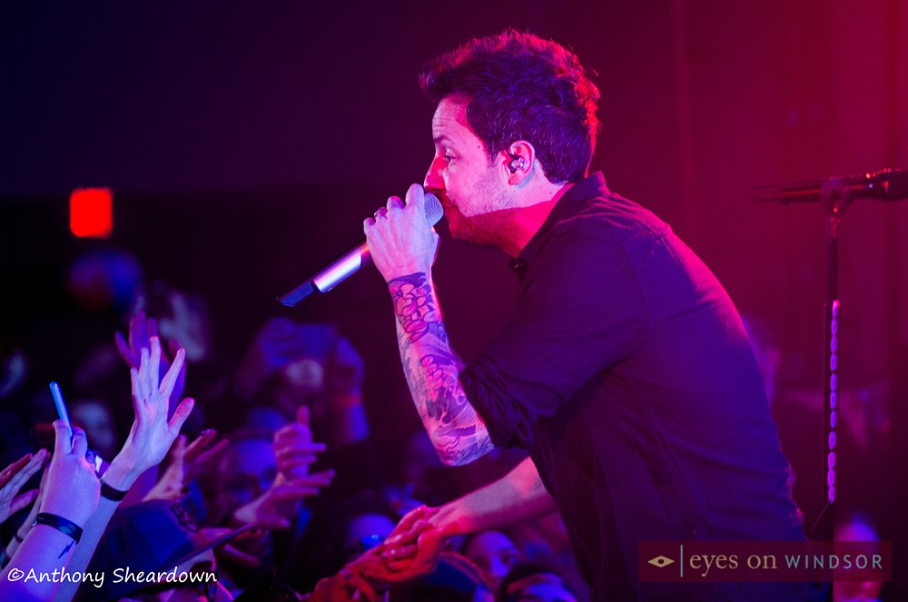 Pierre Bouvier of Simple Plan sings during concert at Olde Walkerville Theatre while shaking hands with fans.