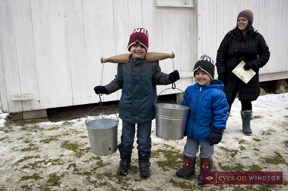 Children carry maple syrup buckets like the pioneers did in years past.