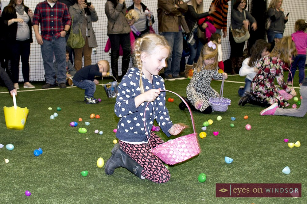 young girl collects chocolate easter eggs.