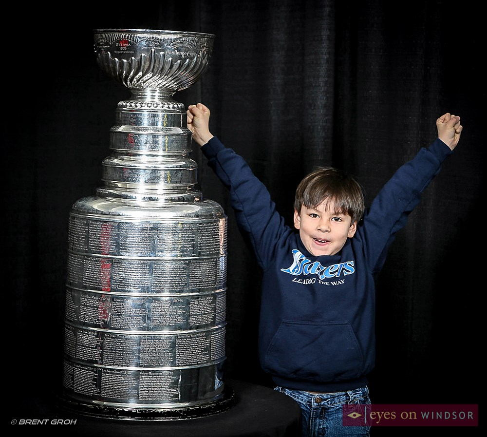 Young boy with hands in the air excited to stand next to the Stanley Cup.