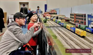 Father and son watching model train go by.