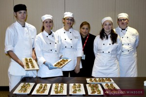 Assumption College Catholic High School students holding up hors d'oeuvres they prepared.