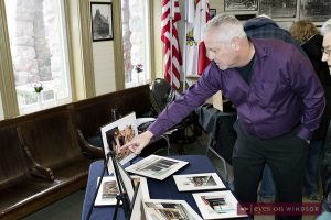 Essex Free Press reporter Fred Groves points to photograph of 1980 natural gas explosion in the Town of Essex while at the Essex Railway Station during the Blasts From Our Past exhibit.
