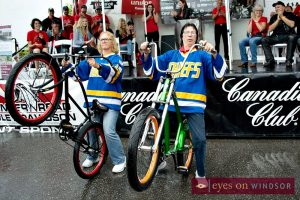 Hanson Brothers riding vintage bicycles while popping a wheelie during the annual Bob Probert Ride in Windsor.