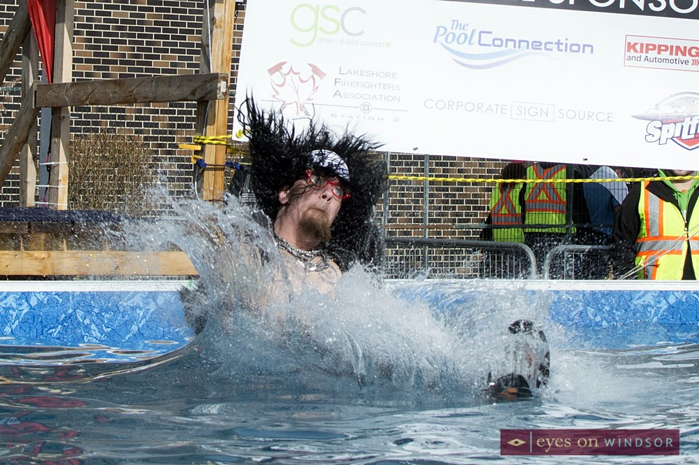 Polar Plunge participant dressed as Rock Star  makes a splash in icy pool.