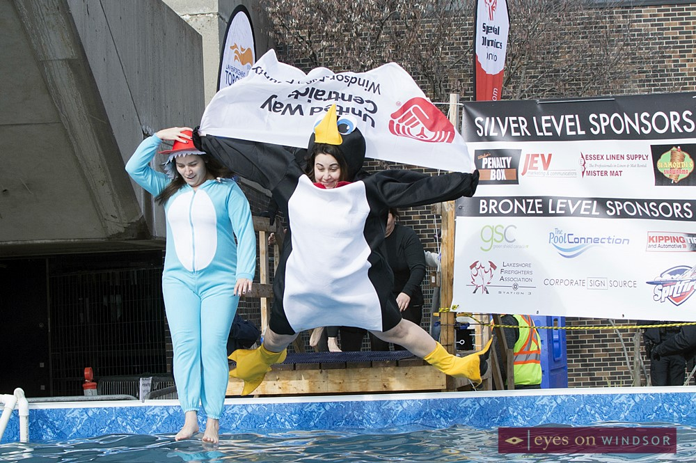 Windsor Essex United Way members dressed in costume leaping into icy pool water.