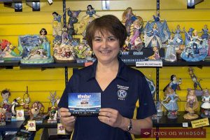 Kiwanis Club of Windsor Treasurer Pearl Davies during Free Comic Book Day 2017 at Cartoon Kingdom holding up Windsor ComiCon post card explaining that Kiwanis Sunshine Point Camp will benefit from this year's ComiCon.