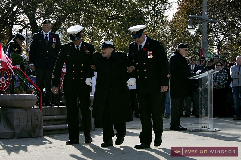 Elderly female veteran assisted to here seat after placing a wreath at Windsor cenotaph.
