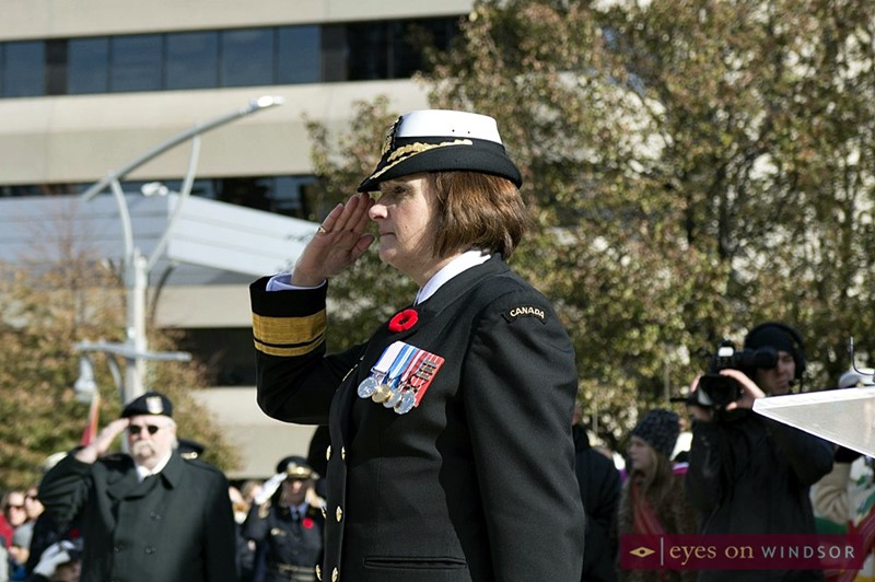 Female military member salutes during Remembrance Day ceremony.