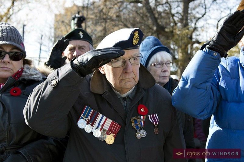 Veteran salutes during Remembrance Day ceremony in Windsor, Ontario.