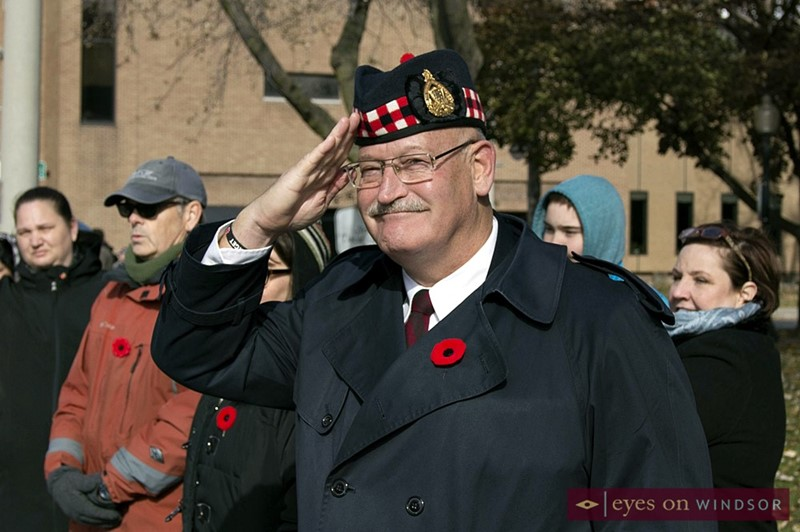 Member of military sautes parade as it passes by in Windsor during Remembrance Day.