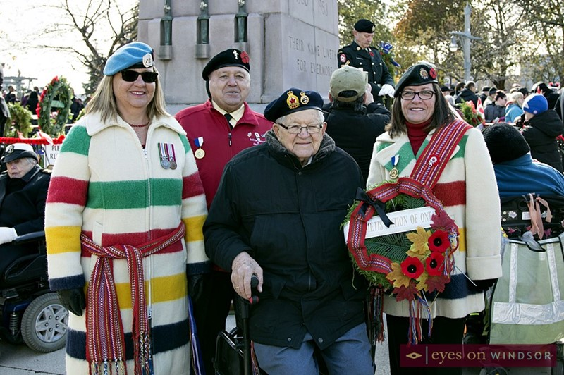 Military veteran with her family in front of Windsor cenotaph after Remembrance Day ceremony.