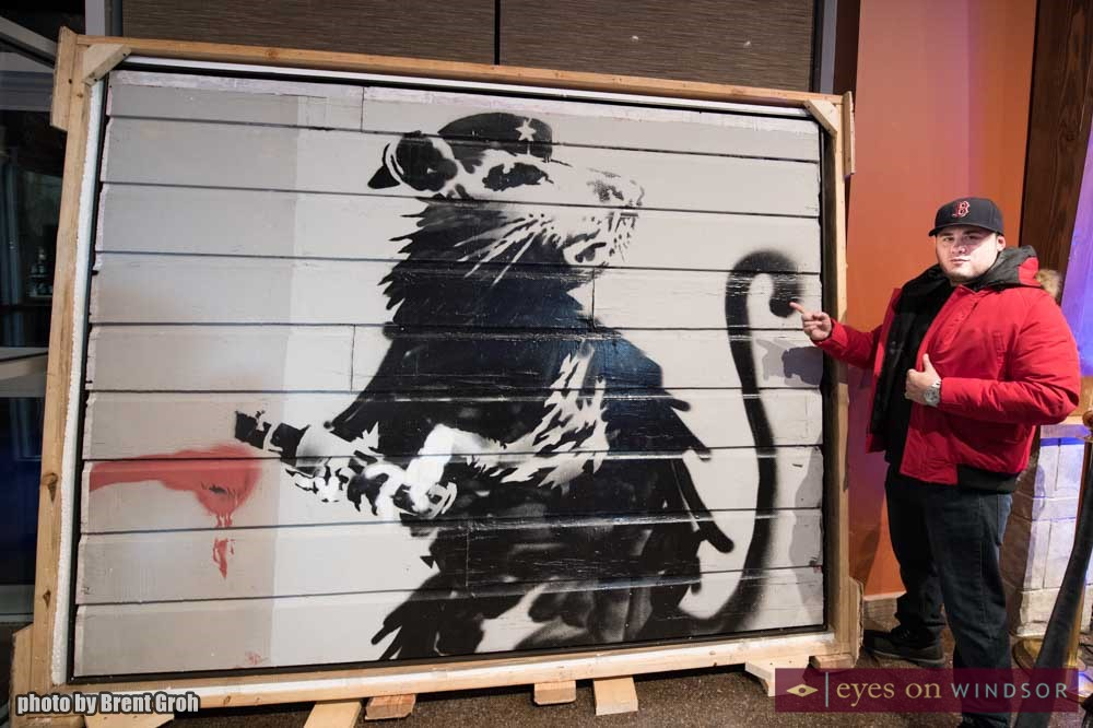 Jason Freed stands next to Haight Street Rat part of the Saving Banksy exhibit on display at Wolfhead Distillery