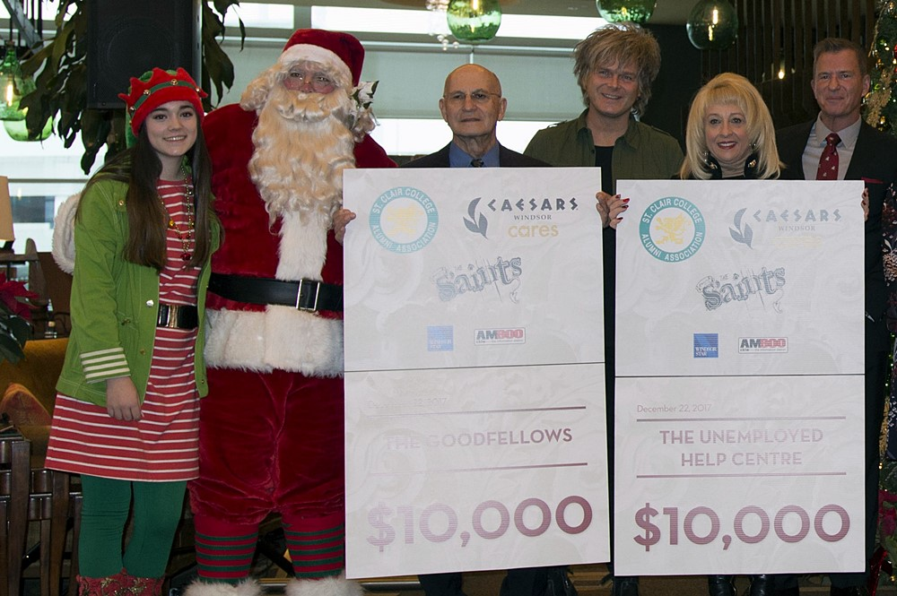 Santa and His Elf with Drummer Jeff Burrows of the S'Aints, Tim Trombley, Director of Entertainment, Caesars Windsor, with members of The Unemployed Help Centre and Windsor Homes Coalition.