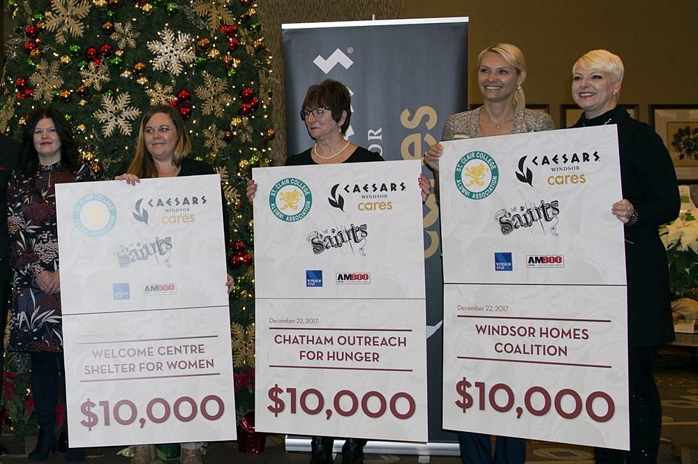 Chatham Outreach for Hunger, Welcome Shelter for Women and the Windsor Homes Coalition hold up checks they received during the Sleighing Hunger Concert Fundraiser check presentation.