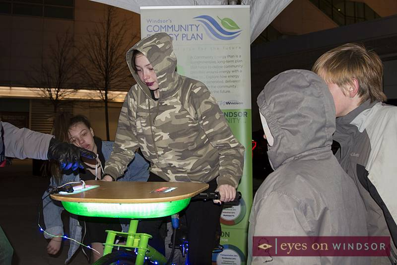 Young girl rides stationary bike generating electricity at the Windsor Community Energy Plan display on Earth Hour at Charles Clark Square