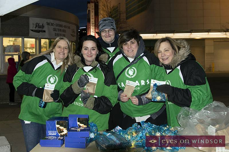 Caesars Windsor employees volunteering during Earth Hour hand out candles and plant seeds at Charles Clark Square