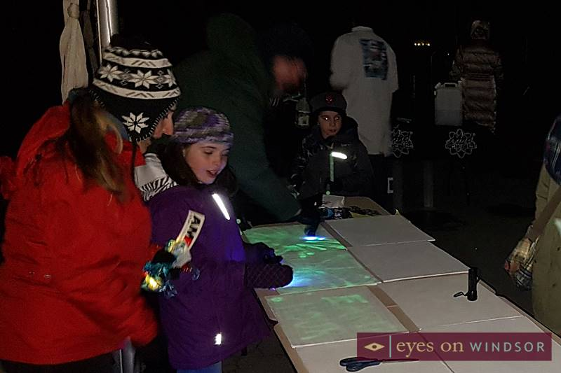 Young girl enjoy interactive painting with light art activity during Earth Hour at Charles Clark Square