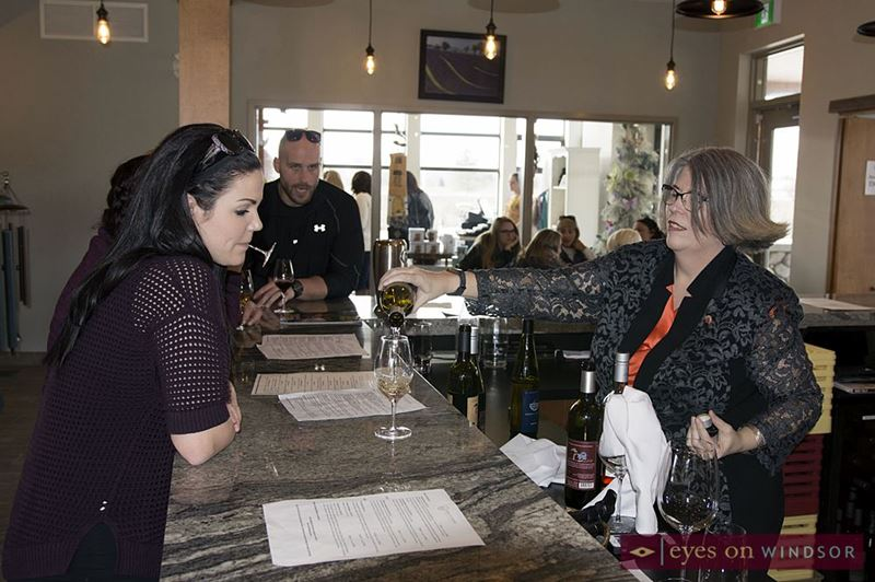 Host pours a glass of North 42 Degree Estate Winery wine for guests.