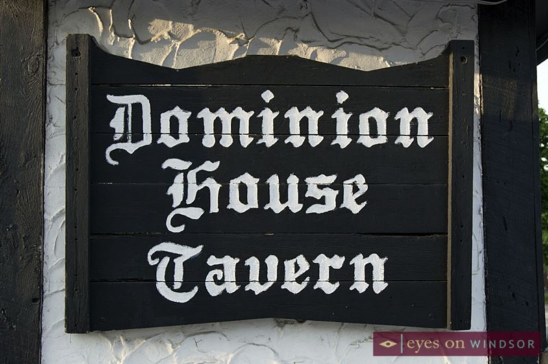 Dominion House Tavern Sign on the building's outside wall.