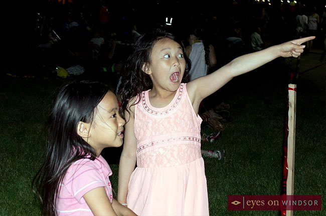 Young girl points to the annual Ford City Fireworks going off in the sky.