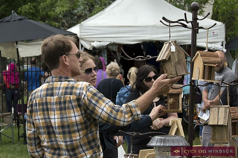 People looking at hand crafted bird houses at Art In The Park Windsor.