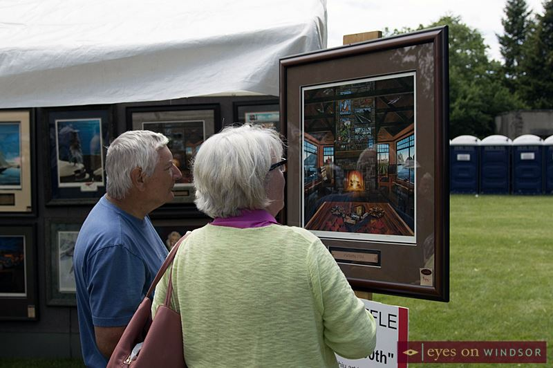 A couple looks at the artwork of local artist Ronald Suchiu during Art In The Park.