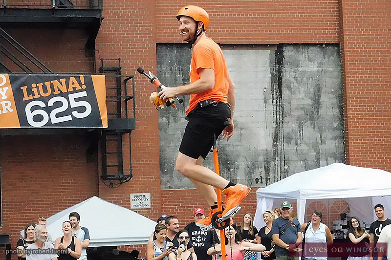 Wacky Chad smiles as he prepares to juggle while riding a tall unicycle at the Buskerville Fest in Windsor, Ontario,