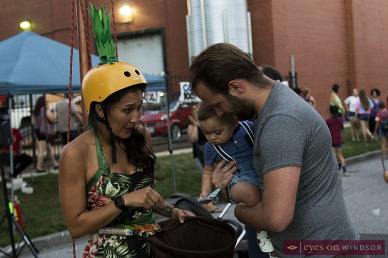 The Flyin' Hawaiian, Sara Kunz , receives a five dollar tip from a baby boy and his father during the inaugural Buskerville Festival