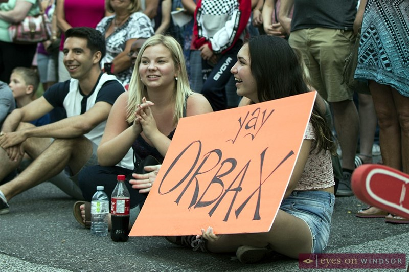 Young lady holds up a sign cheering on Orbax of The Monsters of Schlock during the their performance