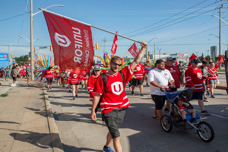 Windsor Labour Day Parade participant holding Unifor Flag.