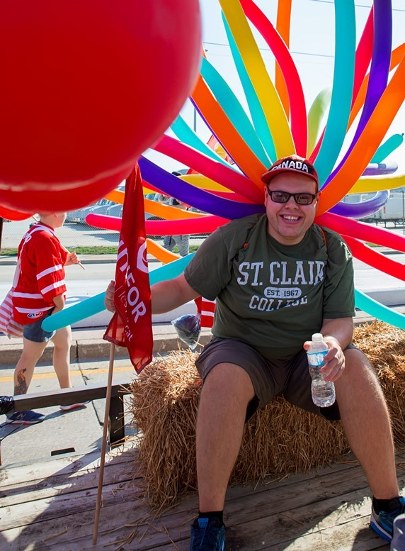 Young man sits on a float as it passes by during the annual Labour Day Parade in Windsor, Ontario