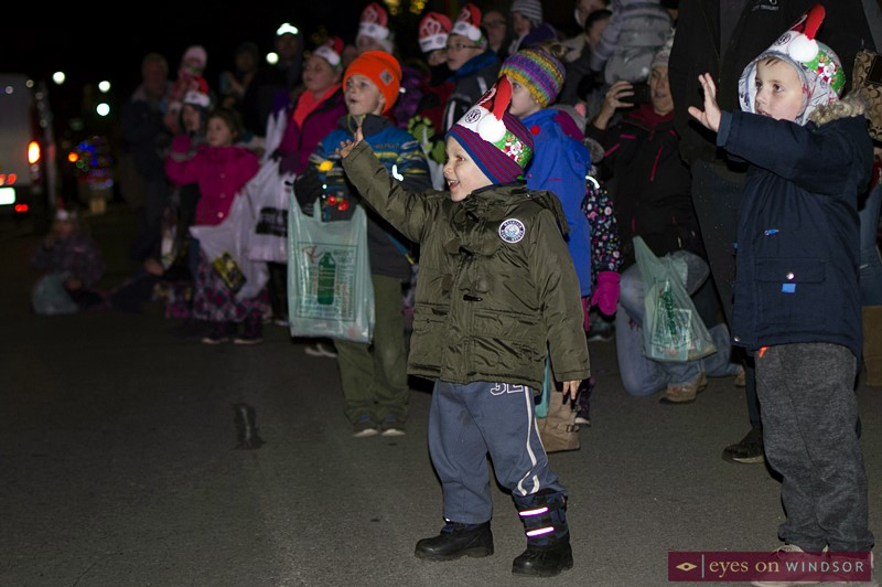 Children waving during Kingsville Santa Claus Parade.