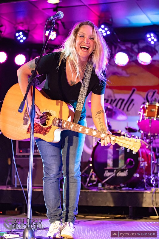 Sarah Smith smiling while playing the guitar