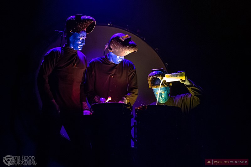 Blue Man Group pouring colourful paint onto drums.