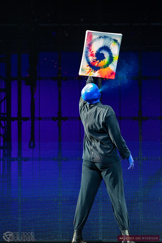 Blue Man Group performer creating abstract art painting