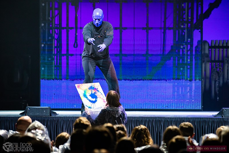 Blue Man Group Character Gives Abstract Art To Audience Member