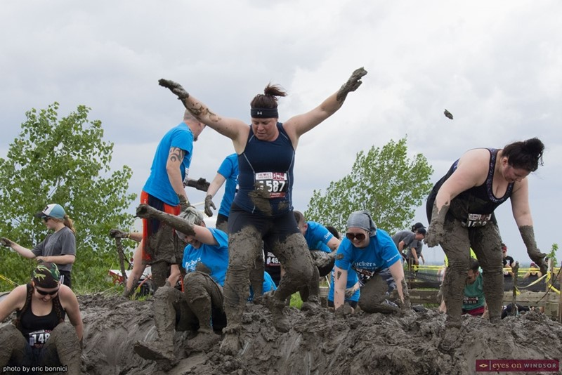 Heart Breaker Challenge participants climbing over a mud hill.