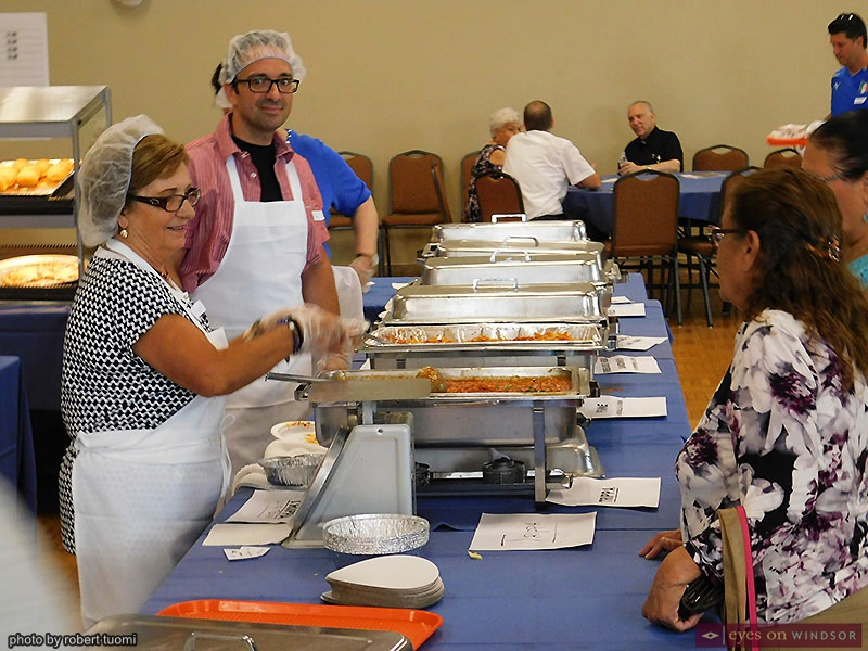 People serving food in the St. Angela Merici Church Hall