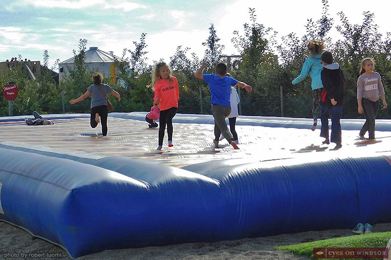 kids jumping on a bouncy trampoline at Thiessen Orchards